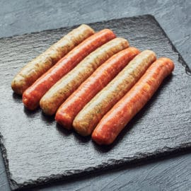 Raw butchers sausages on slate. Overhead view