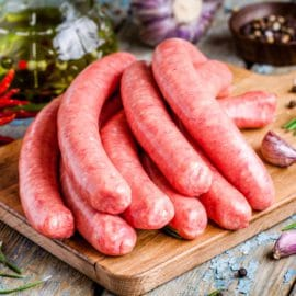 raw homemade sausages on cutting board  with rosemary and garlic